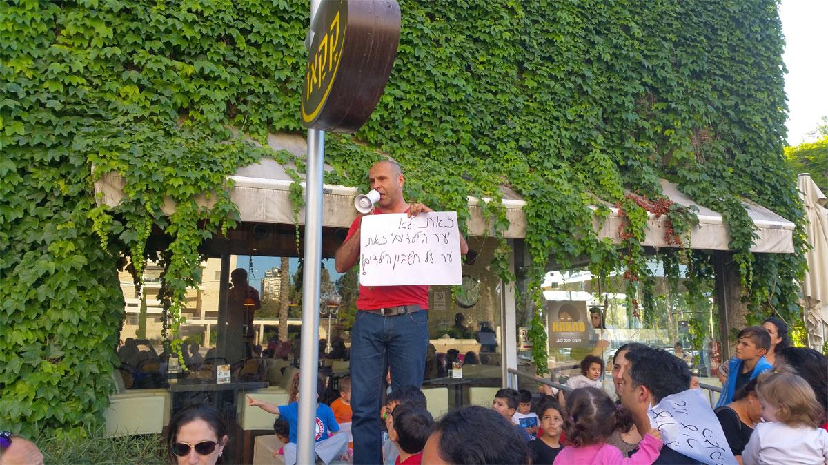חבר המועצה עזרא סיטון נואם בהפגנה